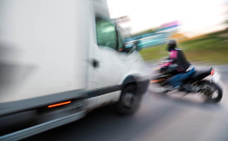 轻型厢式货车与后方由谢某驾驶的摩托车发生碰撞